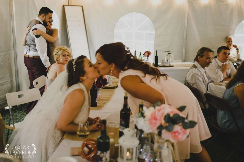 Candid wedding photo of bride and mom kissing