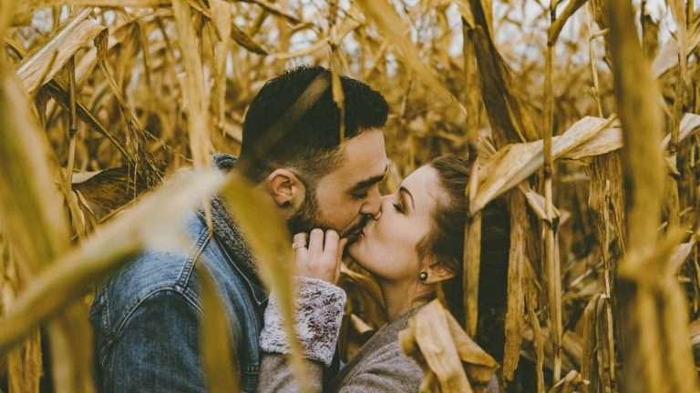 Couple kissing inside corn field
